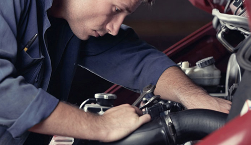 Man in blue overalls working on a car service