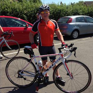 Darren Warman in red top holding bike